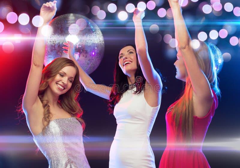 Drie glimlachende vrouwen die in de club dansen stock foto