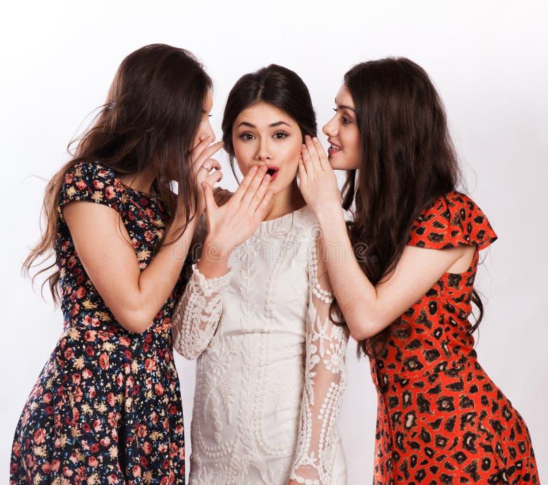 Drie glimlachende vrouwen die roddel fluisteren royalty-vrije stock foto