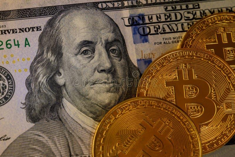 Drie gouden beetje-muntstukken bovenop honderd die dollarsbankbiljet op zwarte achtergrond, cryptocurrency wordt geïsoleerd die  stock afbeeldingen