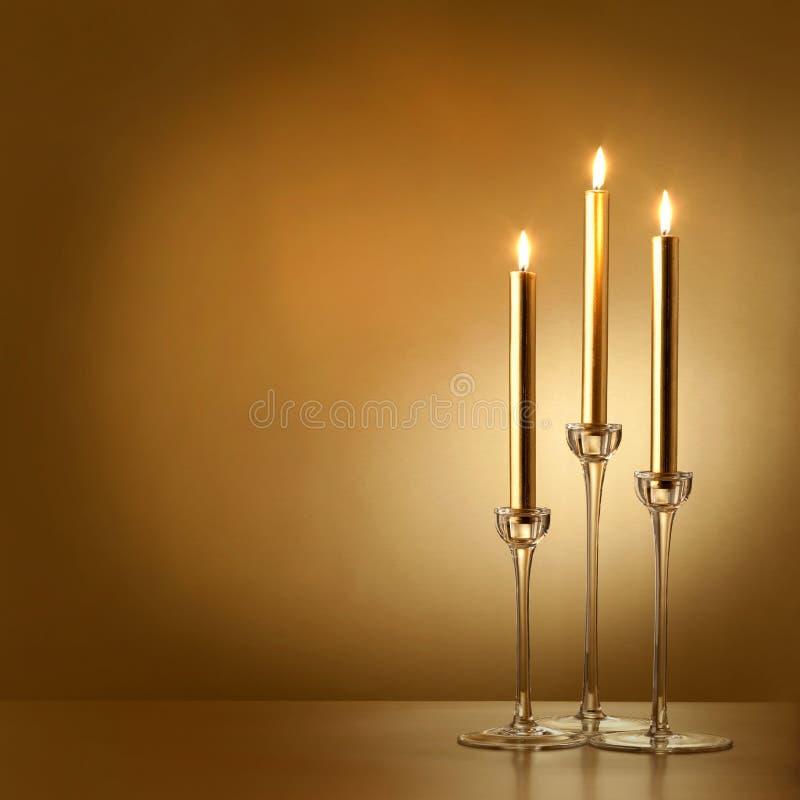 Drie gouden kaarsen stock foto's