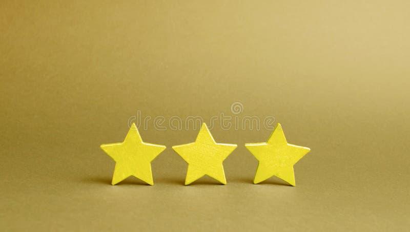 Drie gouden sterren op een gele achtergrond De kwaliteitsdienst, koperskeus Succes in zaken Het concept classificatie stock afbeeldingen