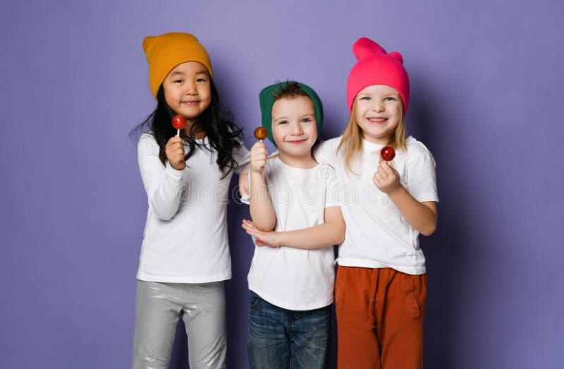 Drie grappige jonge geitjesvrienden in witte t-shirts en kleurrijke hoeden hielden hun te eten spel tegen genieten van suikergoed stock fotografie