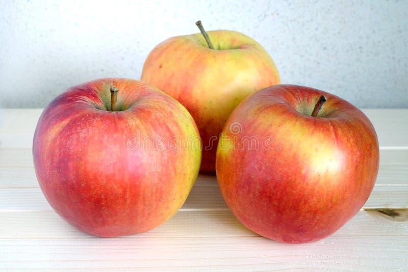 Drie grote rijpe appelen op houten plank stock afbeeldingen