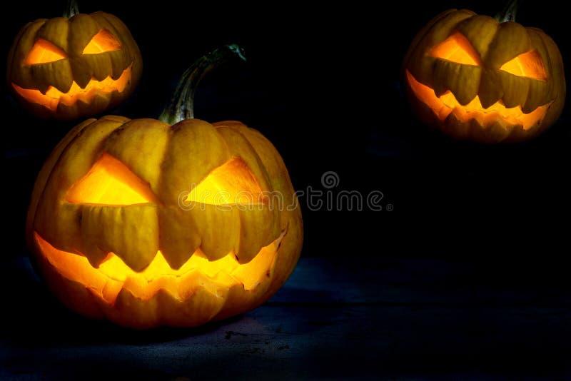 Drie Halloween-pompoenen hoofdhefboom in partijnacht stock afbeeldingen