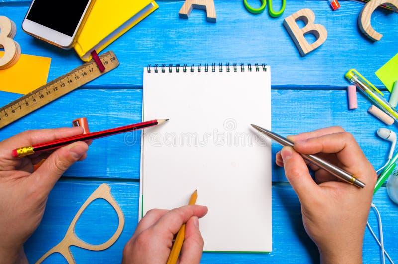 Drie handen met potloden en pennen richten aan een notitieboekje met witte pagina's op de Desktop blauwe houten achtergrond Creat stock afbeelding