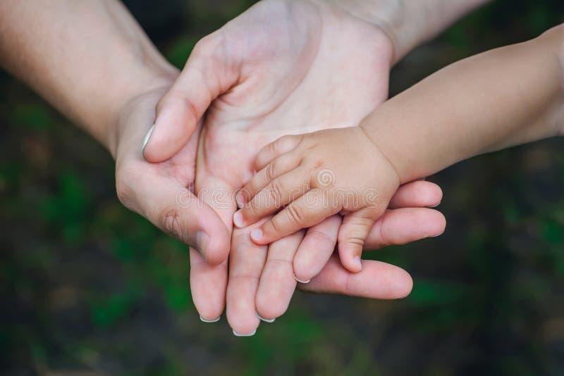 Drie handen van dezelfde familie - de vader, de moeder en de baby blijven samen Het concept familieeenheid, bescherming, steun royalty-vrije stock fotografie