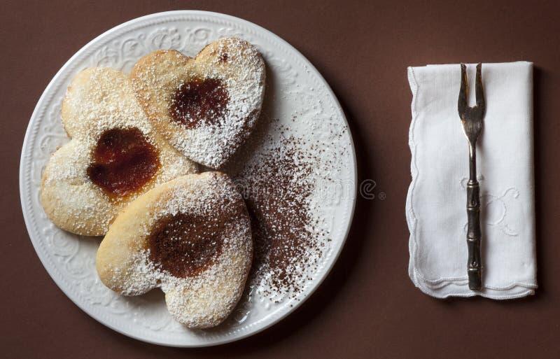 Drie hart-vormige koekjes met jam op een plaat Servet en vork stock foto