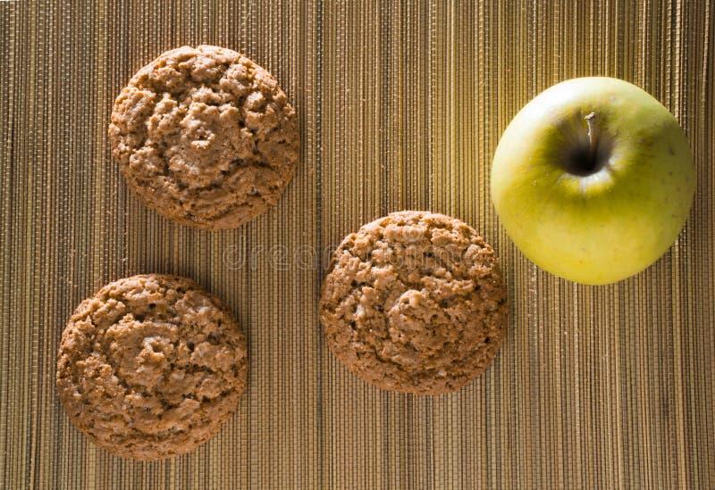 Drie havermeelkoekjes met appel op een bamboemat stock fotografie