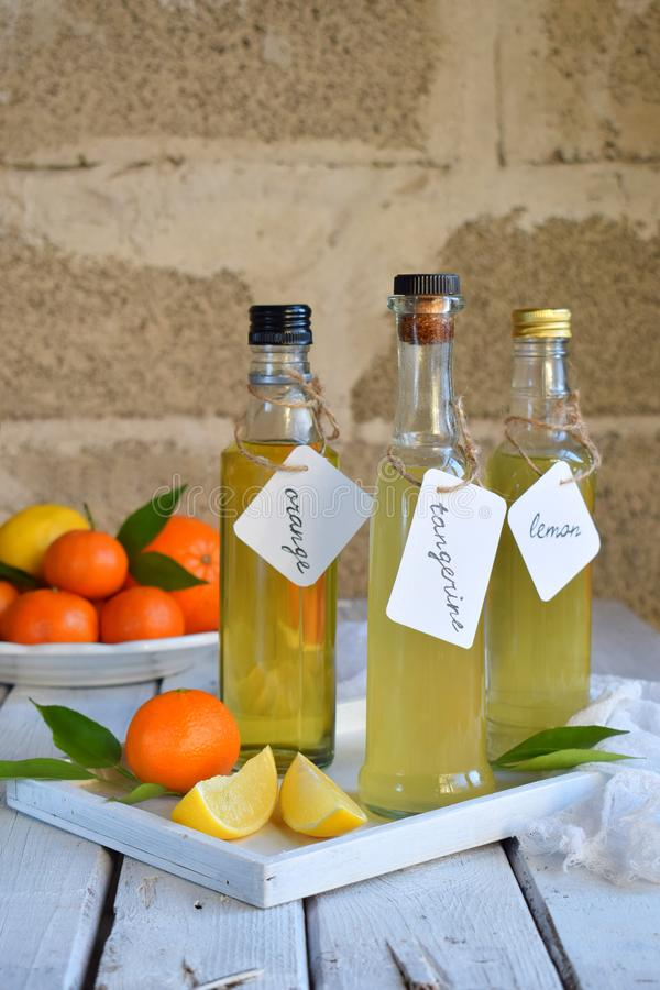 Drie heerlijke gele alcoholdranken in glasflessen en citrusvruchten Oranje-op smaak gebrachte likeur, Italiaanse Limoncello-alcoh stock afbeelding