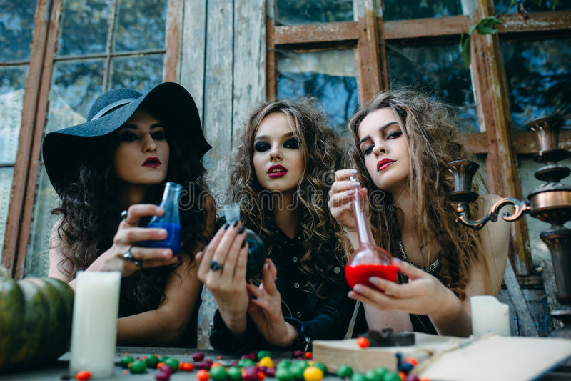 Drie heksen bij de lijst stock afbeeldingen