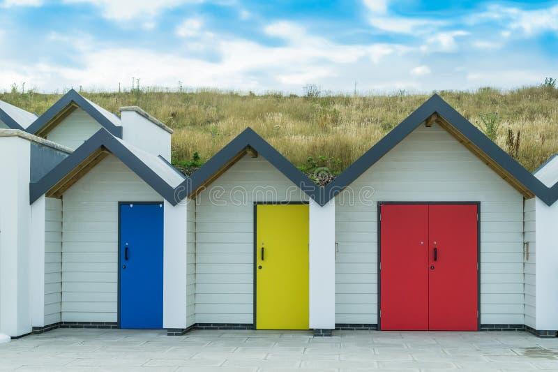 Drie helder gekleurde strandhutten in Swanage in Dorset stock foto's