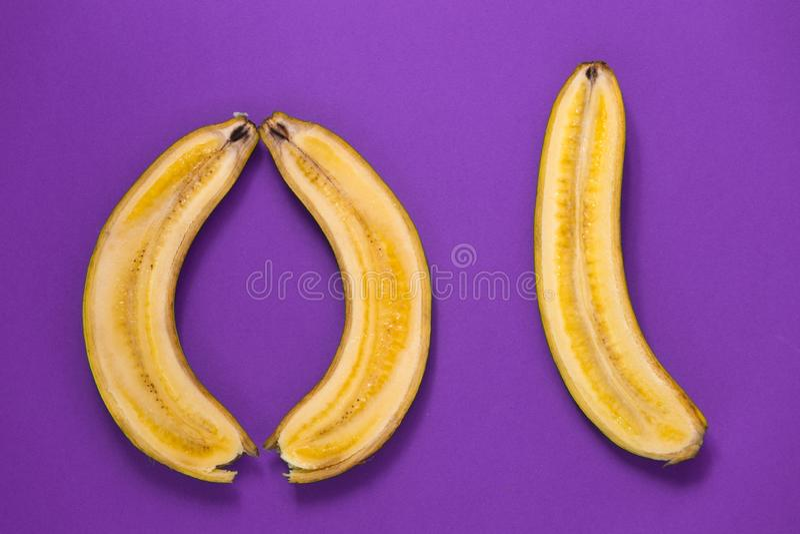 Drie helften van een banaan op een paarse achtergrond royalty-vrije stock foto's