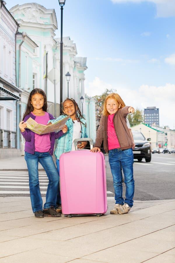 Drie het glimlachen meisjestribune met kaart en bagage stock afbeeldingen