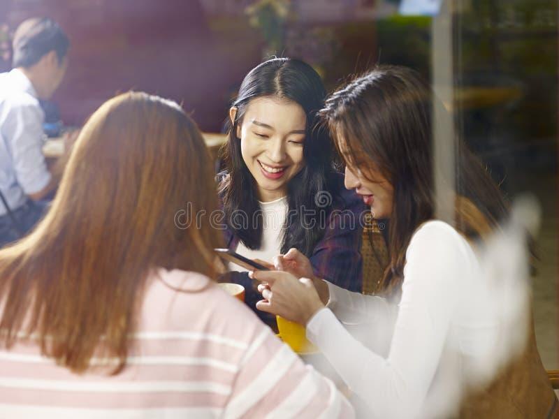 Drie het jonge Aziatische vrouwen babbelen die in koffiewinkel spreken stock afbeelding
