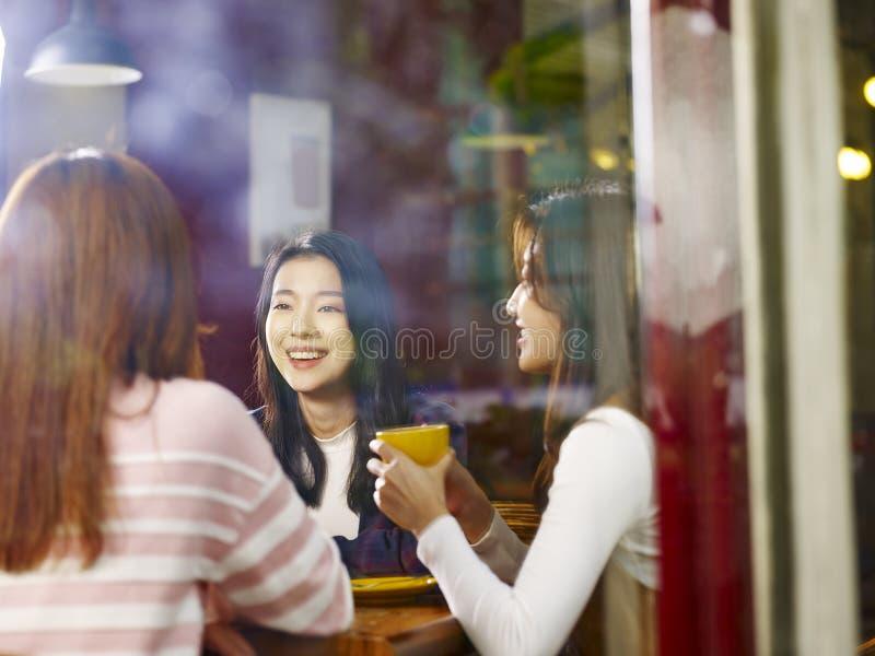 Drie het jonge Aziatische vrouwen babbelen die in koffiewinkel spreken stock foto
