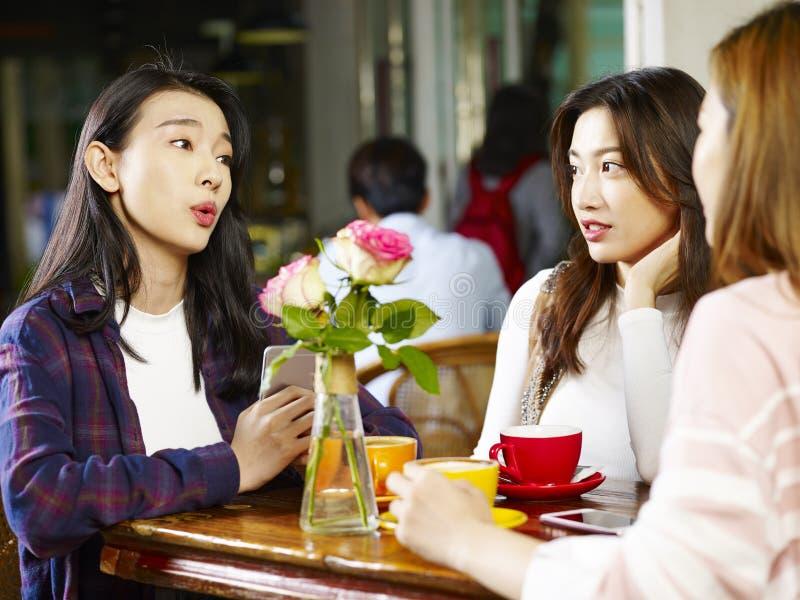 Drie het jonge Aziatische vrouwen babbelen die in koffiewinkel spreken stock fotografie
