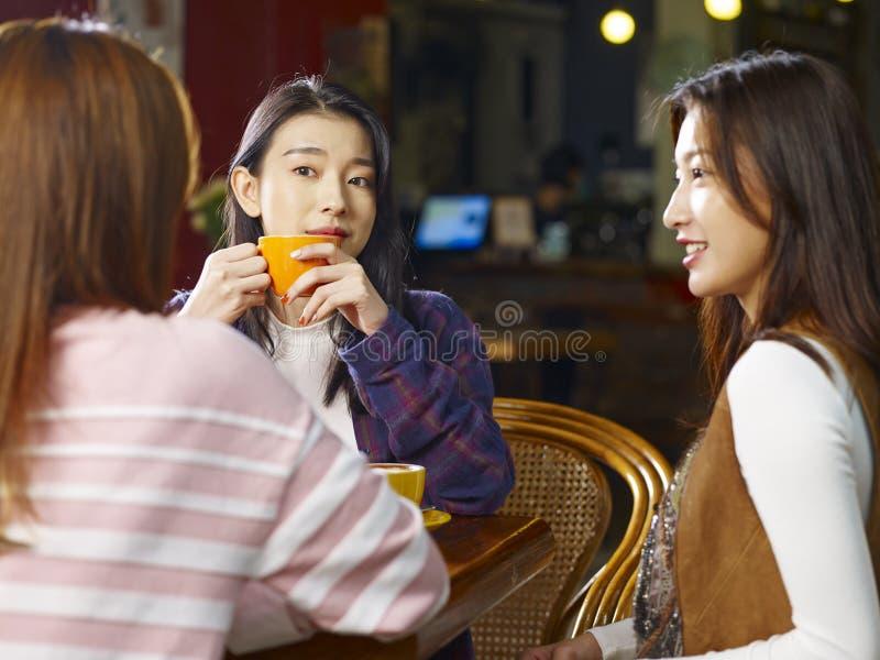 Drie het jonge Aziatische vrouwen babbelen die in koffiewinkel spreken royalty-vrije stock foto