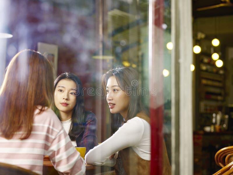 Drie het jonge Aziatische vrouwen babbelen die in koffiewinkel spreken royalty-vrije stock afbeeldingen