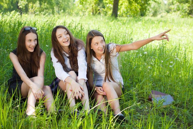 Drie het mooie meisje van de glimlachstudent in het park royalty-vrije stock fotografie