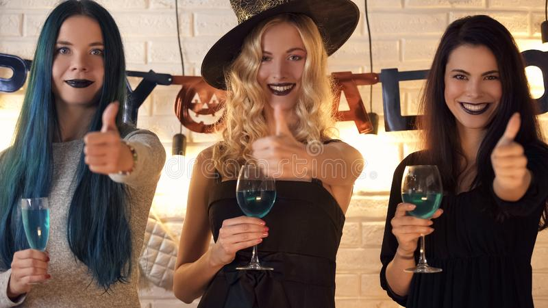 Drie het mooie vrouwen beduimelt tonen gebaar, die pret op Halloween-vooravond omhoog hebben stock afbeeldingen
