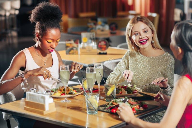 Drie het succesvolle jonge vrouwen samen opgewekt voelen hebbend diner stock afbeeldingen