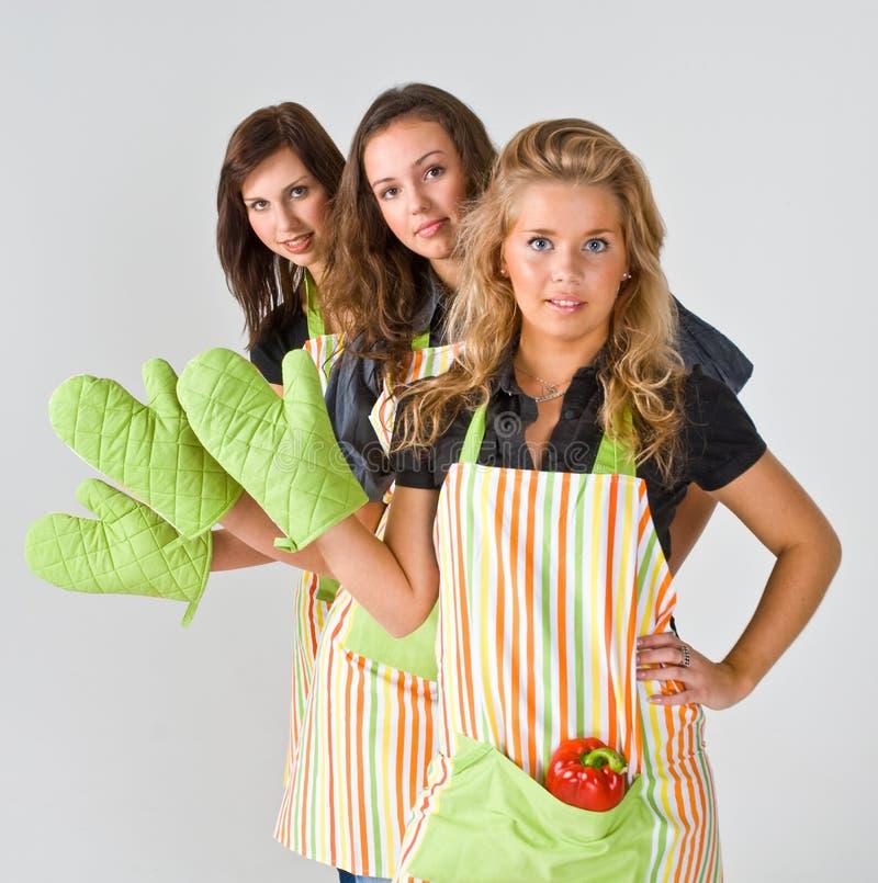 Drie het vrouwelijke koks begroeten stock afbeeldingen