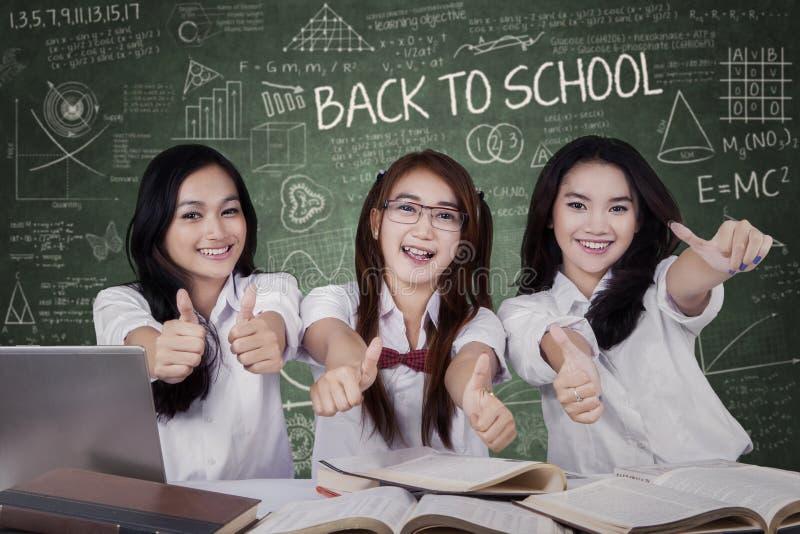 Drie het vrouwelijke studenten omhoog beduimelt tonen stock afbeeldingen
