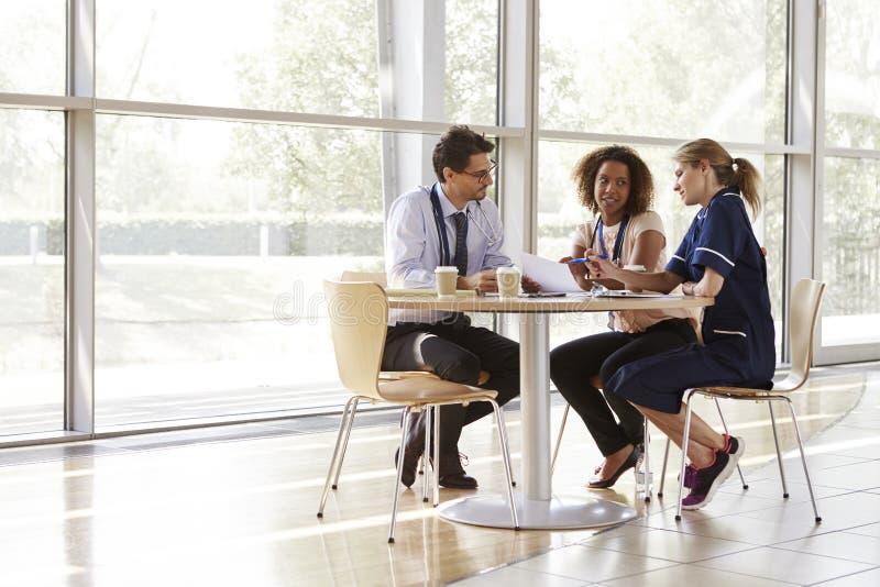 Drie hogere gezondheidszorgarbeiders in een vergadering stock foto