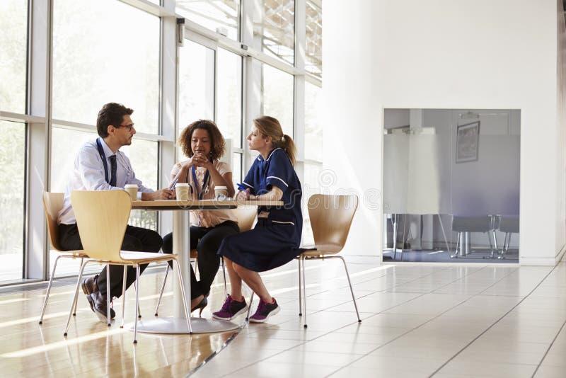 Drie hogere gezondheidszorgarbeiders in een vergadering, lage hoek stock afbeeldingen