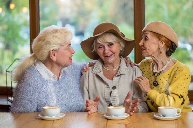 Drie hogere vrouwen in koffie stock afbeeldingen