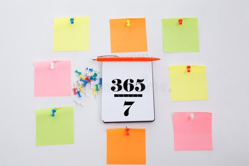 Drie honderd vijfenzestig zeven dagen Het concept schrijft op Bureaulijst, blocnote en kleurrijk potlood Mening van hierboven met royalty-vrije stock foto's