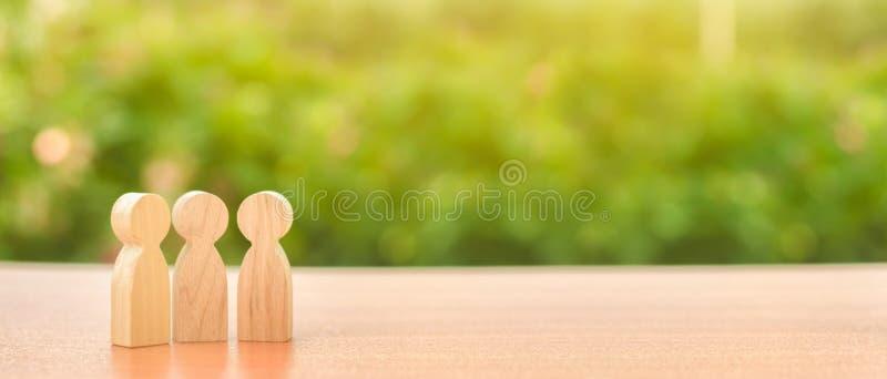 drie houten cijfers van mensentribune op de achtergrond van aard Mededeling, samenkomende plaats Leid een gesprek bespreking royalty-vrije stock fotografie
