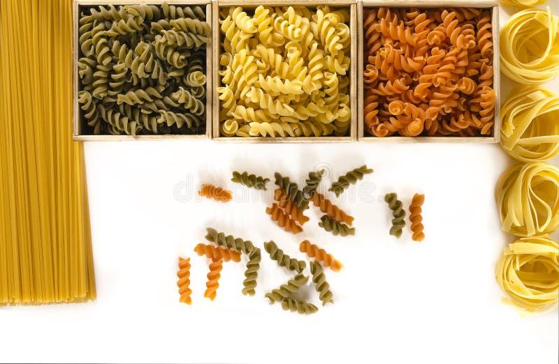 Drie houten dozen met gekleurde fusilli zijn op een witte achtergrond naast spaghetti en tagliatelle stock foto's