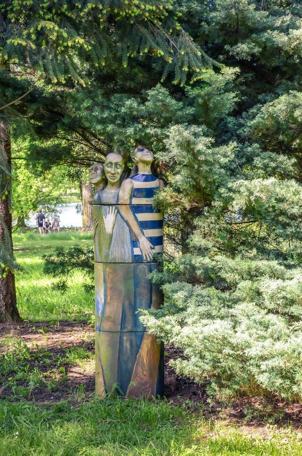 Drie houten meerminnen die onder een boom zitten royalty-vrije stock afbeeldingen