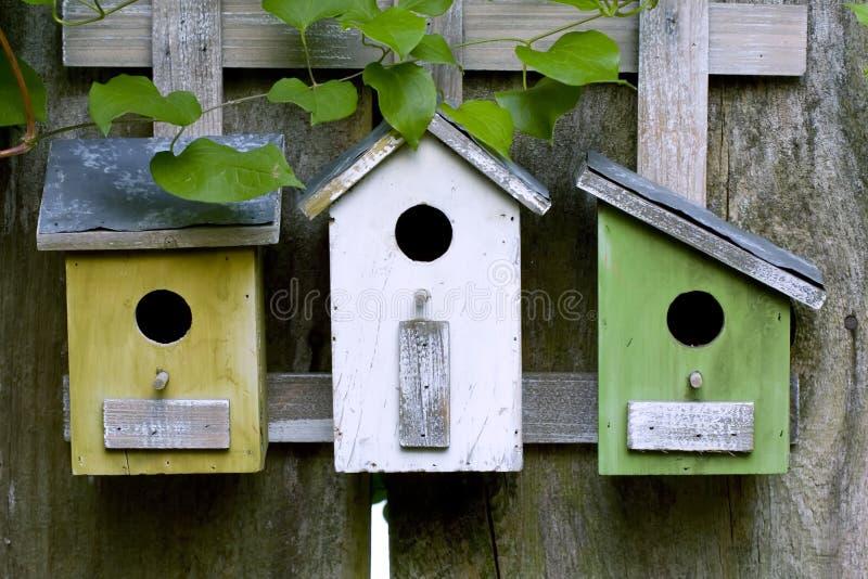 Drie houten vogelhuizen stock afbeelding
