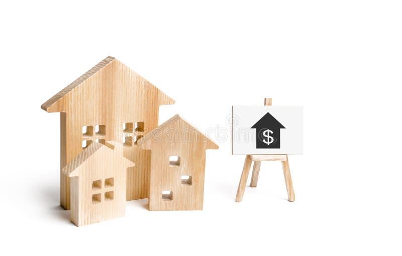 Drie huizen en een teken op een witte achtergrond Het kopen en het verkopen van onroerende goederen, bouw Flats en flats stock foto