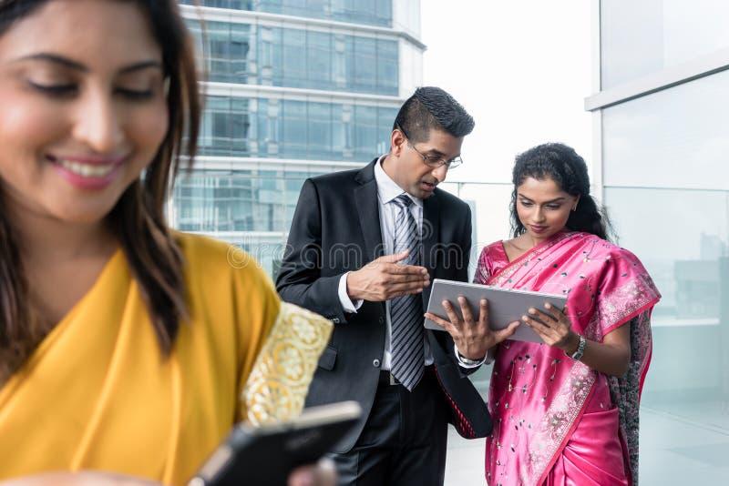 Drie Indische bedrijfsmensen die moderne apparaten binnen met behulp van stock foto