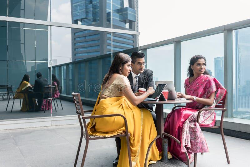 Drie Indische bedrijfsmensen die tijdens onderbreking op het werk spreken stock afbeelding