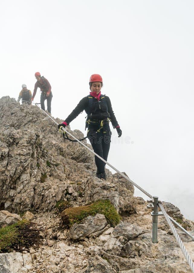 Drie jonge aantrekkelijke vrouwelijke en mannelijke alpinisten in het Dolomiet van Italië royalty-vrije stock afbeeldingen