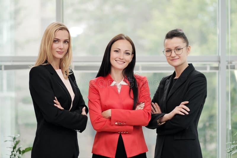 Drie jonge aantrekkelijke vrouwen in pakken die tegen de achtergrond van een licht bureau stellen Hoofd en ondergeschikten stock afbeeldingen
