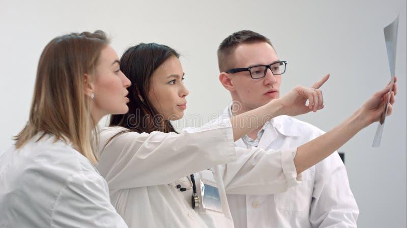 Drie jonge artsen die stekelröntgenstraal bekijken stock foto