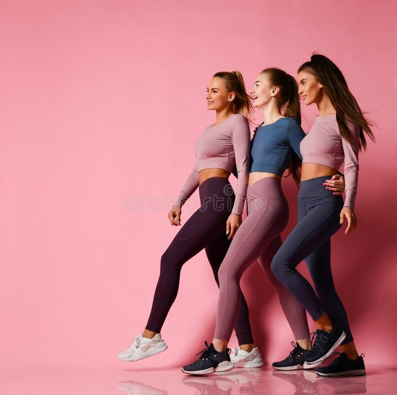 Drie jonge atletische meisjes in high-tech moderne kleurrijke sportkleding lopen krachtig samen naar vrije tekstruimte op roze royalty-vrije stock fotografie