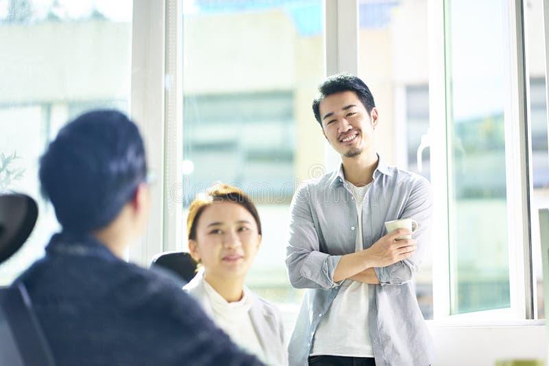 Drie jonge Aziatische bedrijfsmensen die in bureau babbelen stock afbeelding