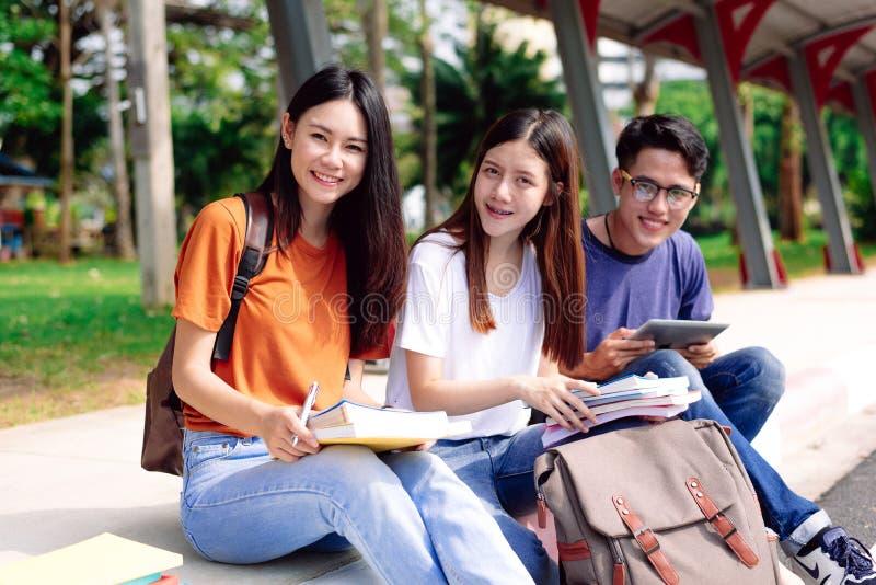 Drie jonge Aziatische mensen die samen in openlucht bestuderen bij Onderwijs en Technologieconcept Levensstijlen en het Gelukkige stock fotografie