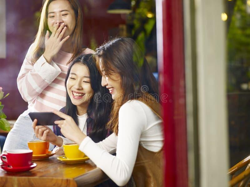 Drie jonge Aziatische mobiele telefoon bekijken en vrouwen die binnen lachen royalty-vrije stock fotografie
