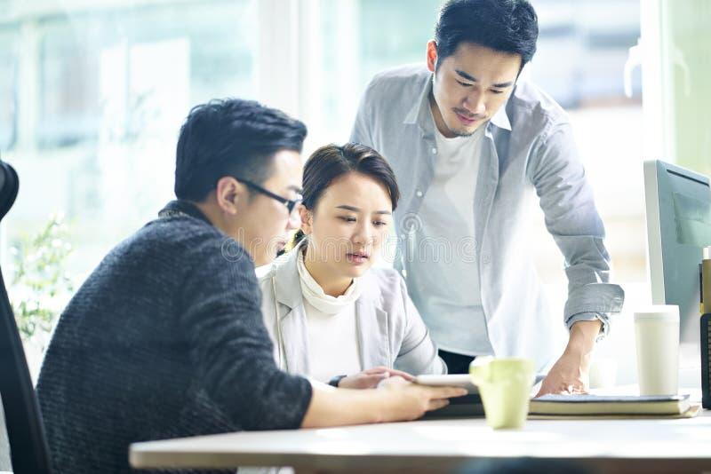 Drie jonge Aziatische ondernemers die zaken in bureau bespreken royalty-vrije stock fotografie