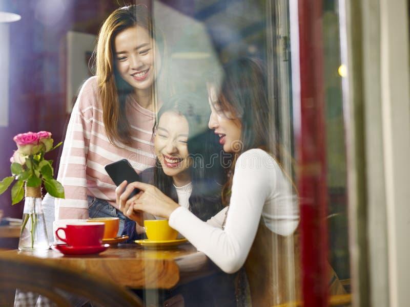 Drie jonge Aziatische vrouwen die mobiele telefoon in koffiewinkel bekijken royalty-vrije stock foto's