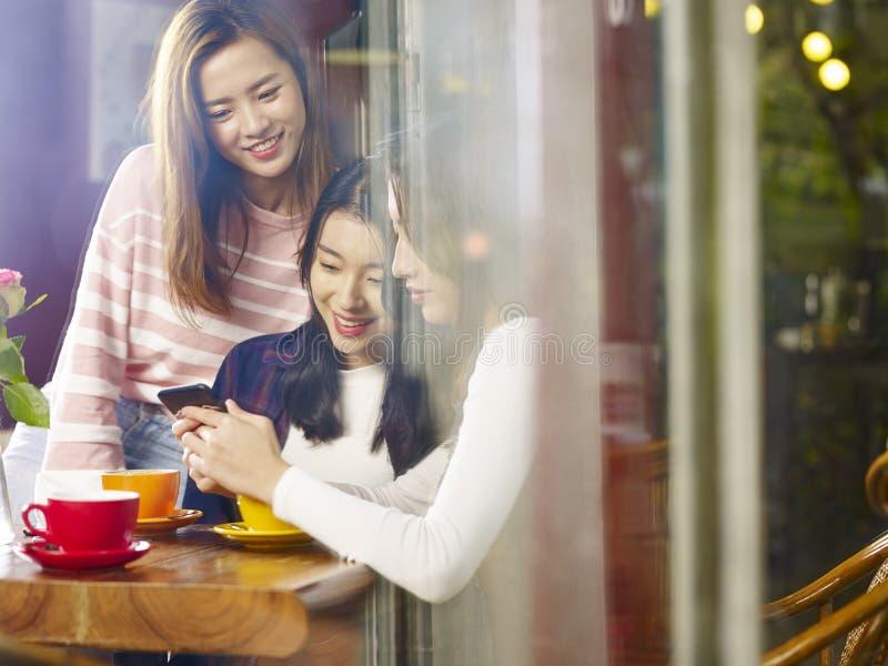 Drie jonge Aziatische vrouwen die mobiele telefoon in koffiewinkel bekijken royalty-vrije stock afbeeldingen