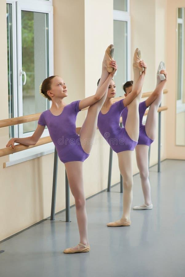 Drie jonge ballerina's die benen uitrekken stock foto