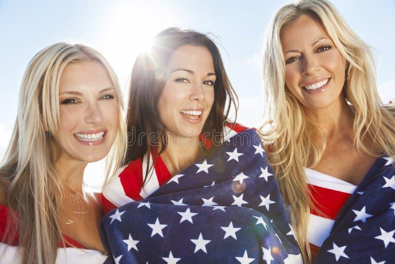 Drie Jonge die Vrouwen in Amerikaanse Vlaggen op een Strand worden verpakt royalty-vrije stock afbeelding